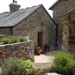 The Old Coach House is accessed via three steps down into a patio coutrtyard.
